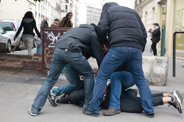 Plain- clothes policemen arrest a man during a protest of students against police brutality, following the alleged rape of Theo in Paris, on February 23, 2017. (Photo by Geoffroy van der Hasselt/AFP Photo)