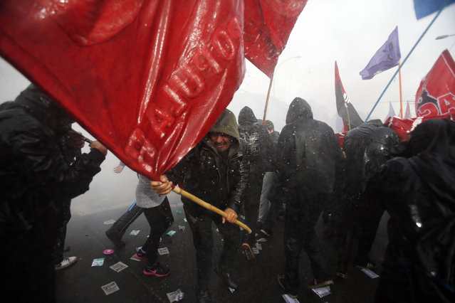 Protestors are sprayed with a water cannon by police near Congress where Chile's President Michelle Bachelet gives her annual address in Valparaiso, Chile, Thursday, May 21, 2015. Demonstrators are demanding more involvement in education reform and protesting the death of two students killed during an education reform march last week in Valparaiso. (Photo by Luis Hidalgo/AP Photo)
