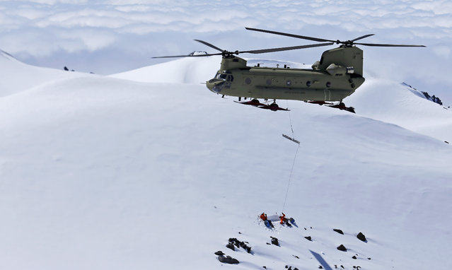 In this photo taken May 15, 2015, a U.S. Army Reserve Boeing CH-47F Chinook helicopter hoists an empty litter prepared by two U.S. Air Force pararescue specialists, anchored in the snow below, at about 9,000 feet above sea level at Mount Rainier in Washington state during a search and rescue training mission. (Photo by Ted S. Warren/AP Photo)