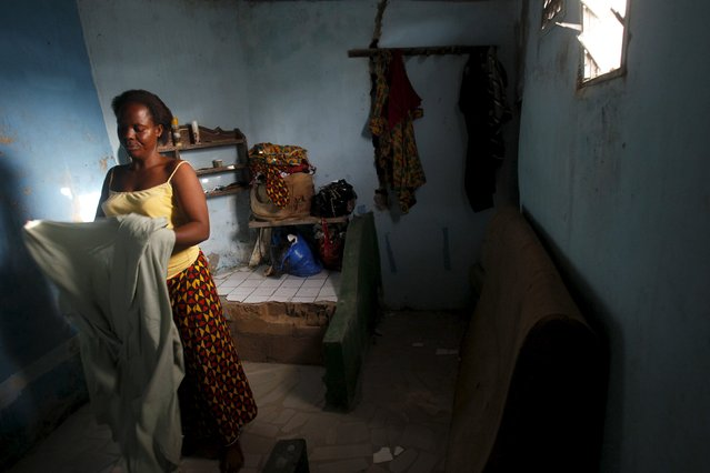 Nicole Gbalou, 31, arranges her clothes at her home in the Cocody Danga slum in Abidjan May 25, 2015. (Photo by Luc Gnago/Reuters)