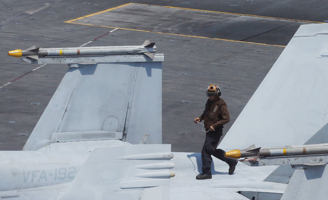 A U.S. Navy crewman prepares a F18 fighter jet on the deck of the U.S. Navy aircraft carrier USS Carl Vinson (CVN 70) prior to a patrol off the disputed South China Sea Friday, March 3, 2017. (Photo by Bullit Marquez/AP Photo)