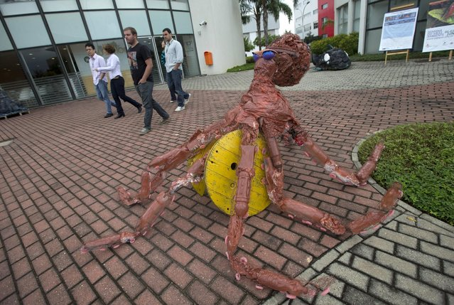 """A sculpture made of trash collected in Guanabara Bay stands on display at the Rio de Janeiro Federal University as part of an exhibit titled """"The Sea Isn't Made for Fish"""" in Rio de Janeiro, Brazil, Monday, June 1, 2015. Around 30 art students used plastic bottles, tires, old flip flops, plastic helmets, scratched CDs, old tubes and plastic supermarket bags to make sculptures of ocean fauna including an octopus and dolphins. (AP Photo/Silvia Izquierdo)"""