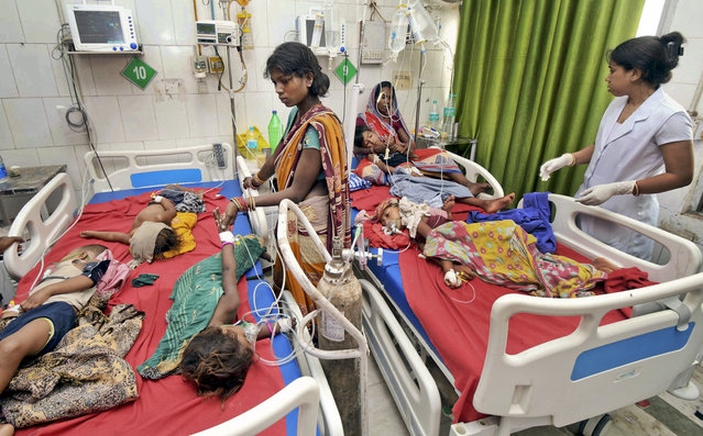 In this Tuesday, June 18, 2019 photograph, children showing symptoms of acute encephalitis syndrome undergo treatment at Sri Krishna Medical College Hospital in Muzaffarpur, Bihar state, India. More than 100 children have died in an encephalitis outbreak in India's eastern state of Bihar, authorities said Tuesday. (Photo by Aftab Alam Siddiqui/AP Photo)