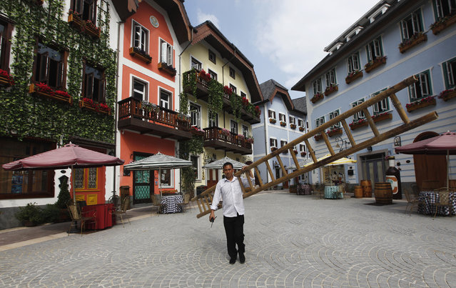 A construction worker walks with a ladder in the replica village of Austria's UNESCO heritage site, Hallstatt, in China's southern city of Huizhou, in Guangdong province June 1, 2012. (Photo by Tyrone Siu/Reuters)