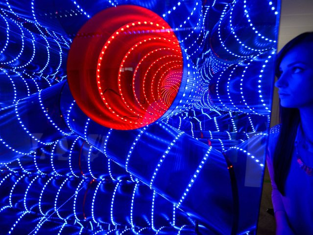 """A woman eyes the work """"Triple Tube (2012/13)"""" by Hans Kotter during Luminale festival of light in Frankfurt, Germany, 29 March 2014. (Photo by Arne Dedert/EPA)"""