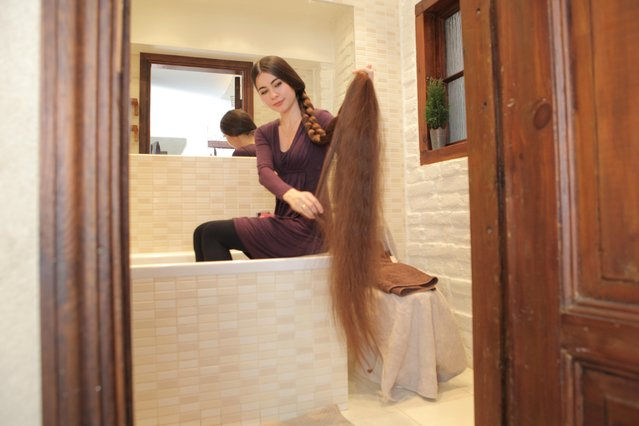 Aliia Nasyrova holding up her 90 inch hair in the bathroom on March 5, 2017 in Riga, Latvia. (Photo by  Eduard Kolik/Barcroft Media)