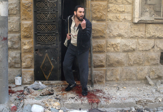 A man reacts as he stands on blood stains at a site hit by airstrikes in the rebel held area of Aleppo's al-Fardous district, Syria, April 29, 2016. (Photo by Abdalrhman Ismail/Reuters)