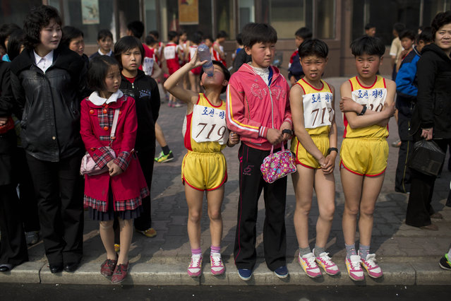 Young North Korean runners rest after finishing their part of the Mangyongdae Prize International Marathon in Pyongyang, North Korea on Sunday, April 13, 2014. The annual race, which includes a full marathon, a half marathon, and a 10-kilometer run, was open to foreign tourists for the first time this year. (Photo by David Guttenfelder/AP Photo)