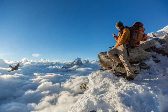 Finding just the right spot above the clouds at Camp 1 on Ama Dablam, Danuru Sherpa uses his iPhone to catch up with friends and family. Even at 18,500 feet (5,654 meters), climbers here can check their email and other dispatches from the world below. (Photo by Aaron Huey/National Geographic)