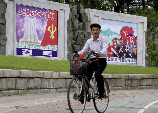 """A cyclist rides past a billboard with the words """"The 7th Congress of the Workers' Party of Korea"""" Thursday, May 5, 2016, in Pyongyang, North Korea. (Photo by Kim Kwang Hyon/AP Photo)"""