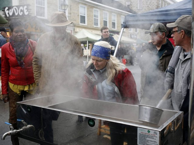 Visitors view a demonstration evaporator during the Perth Maple Festival in Perth, Ontario, Canada, 26 April 2014. The annual maple syrup season marks the end of the often brutal central Canadian winters and heralds the beginning of spring. The maple tree, whose leaf dominates the Canada's flag, plays both a symbolic and practical role in the identity of Canadians who produce around 95 percent of the world's supply of maple syrup. (Photo by Stephen Morrison/EPA)