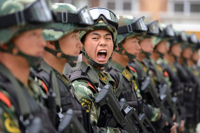 A paramilitary policeman shouts a command during a training session at a base in Taiyuan, Shanxi province, China, May 9, 2014. (Photo by Jon Woo/Reuters)
