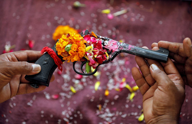 Police officers hold a revolver as they offer prayers to their weapons as part of a ritual at their headquarters on the occasion of Dussehra, or Vijaya Dashami, festival in Ahmedabad, India, October 8, 2019. (Photo by Amit Dave/Reuters)