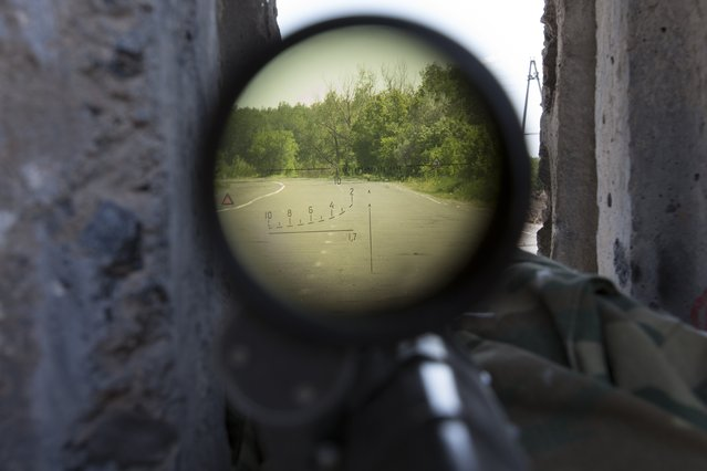 A view through a sniper's rifle from a pro-Russian checkpoint blocking the major highway which links Kharkiv, outside  Slovyansk, eastern Ukraine, Sunday, May 18, 2014. Lawmakers and officials from eastern Ukraine on Saturday poured criticism on the fledging central government, accusing it of ignoring legitimate grievances of the regions which have been overrun by pro-Russia militia fighting for independence. (Photo by Alexander Zemlianichenko/AP Photo)