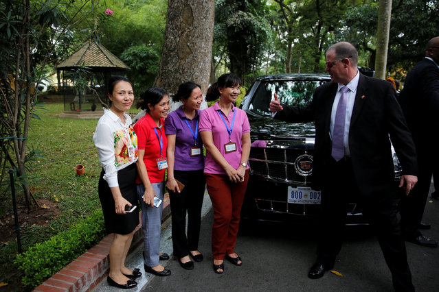 Women pose for a picture next to U.S. President Barack Obama's limousine as a secret service officer asks them to move during Obama's visit at the gardens of the presidential palace in Hanoi, Vietnam May 23, 2016. (Photo by Carlos Barria/Reuters)
