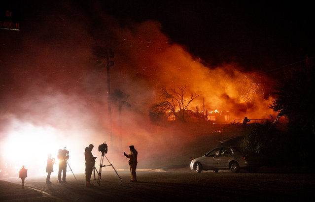 Media members report on a burning home as a firefighter douses flames (R) during the Hillside fire in the North Park neighborhood of San Bernardino, California on October 31, 2019. Firefighters battled new wildfires on in California including a fierce blaze in the city of San Bernardino that forced some residents to flee their homes overnight. The Hillside fire broke out after midnight in San Bernardino, a city of more than 200,000 people some 60 miles (100 kilometers) east of Los Angeles, the San Bernardino County Fire Department said. (Photo by Josh Edelson/AFP Photo)