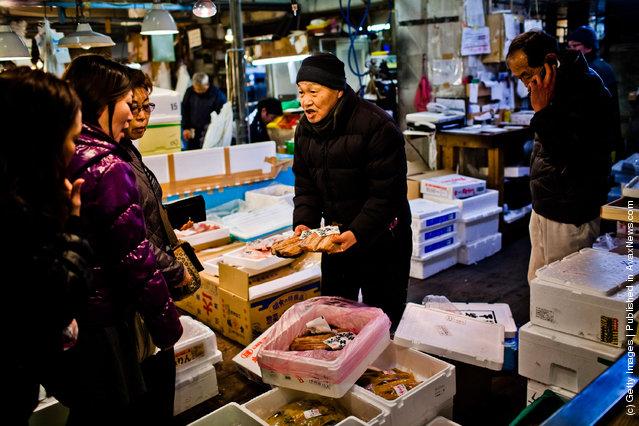 A man displays fish to customers at the Tsukiji fish market
