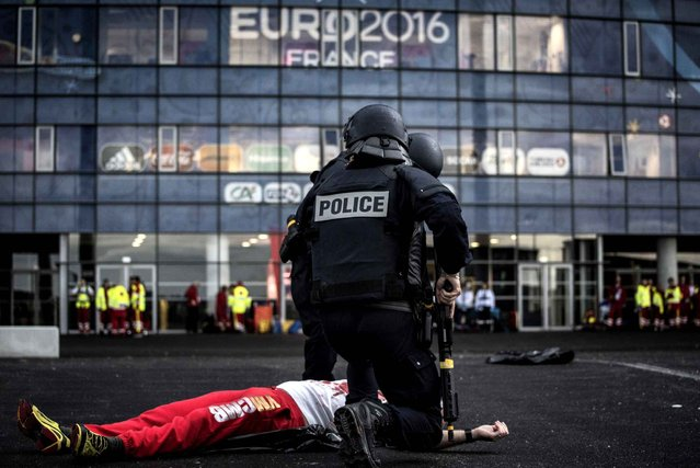 Policemen take part in a mock suicide attack exercise as part of security measures for the upcoming Euro 2016 football championship, at the Parc Olympique Lyonnais stadium in Decines-Charpieu, near Lyon, central-eastern France, on May 30, 2016. (Photo by Jeff Pachoud/AFP Photo)