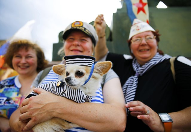 Russian women hold a dog sporting a stylised sailor's shirt and cap during celebrations of the Navy Day in St. Petersburg, Russia, July 26, 2015. (Photo by Reuters/Stringer)
