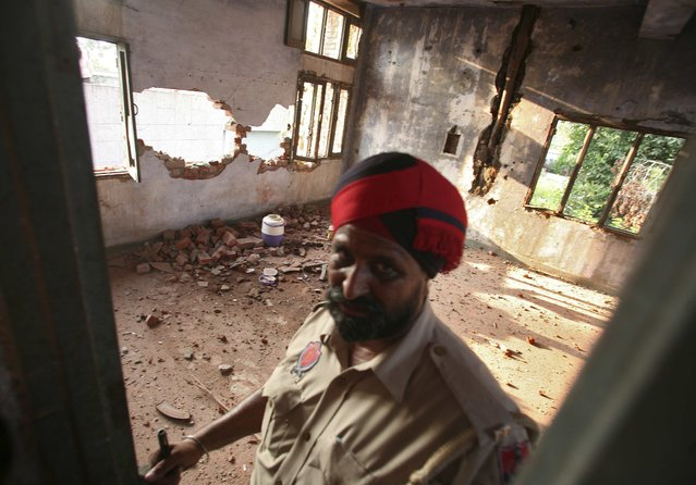 An Indian policeman stands inside a damaged police station after a gunfight in Dinanagar town in Gurdaspur district of Punjab, India, July 27, 2015. (Photo by Munish Sharma/Reuters)