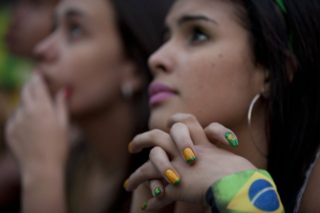 A fan watches the group A World Cup match between Mexico and Brazil via a live broadcast at the FIFA Fan Fest in Sao Paulo, Brazil, Tuesday, June 17, 2014. Forget the French manicure. It's Brazil during World Cup, and women here want to flaunt their love of the national team with wacky nail designs. (Photo by Dario Lopez-Mills/AP Photo)