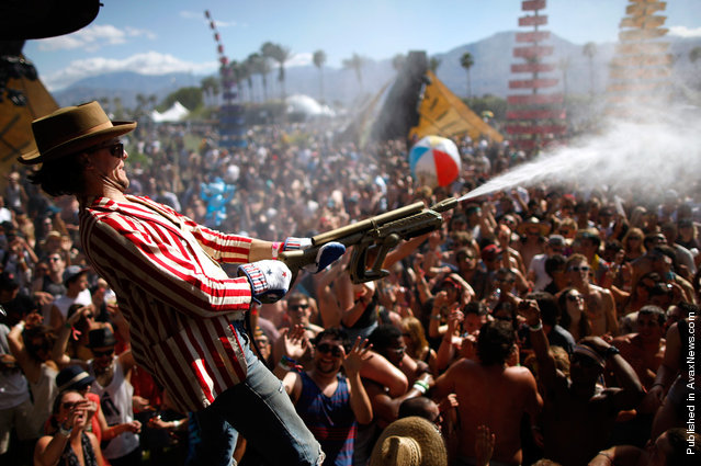 People dance under water sprayed from hoses at the Do Lab at Coachella 2012, on April 14, 2012