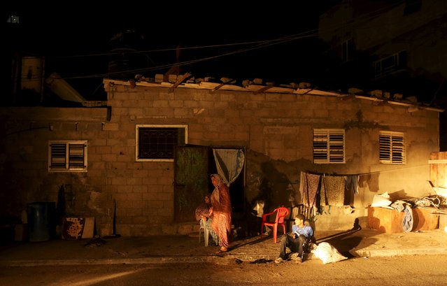 Palestinians gather outside their house as they flee the heat during power cut at Shatti (beach) refugee camp in Gaza City July 23, 2015. (Photo by Mohammed Salem/Reuters)