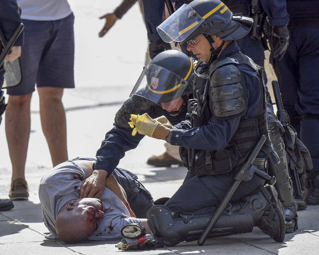 A man lying on the ground is assisted by French policemen during clashes bewteen English and Russian supporters in the Old Port of Marseille, France, Saturday, June 12, 2016, before the UEFA EURO 2016 group B match between England and Russia. (Photo by Daniel Dal Zennaro/ANSA via AP Photo)