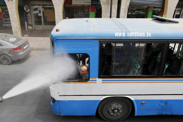 A bus driver reacts as Greater Amman Municipality personnel spray them with a water sprinkler in order to cool them down as part of measures to ease the effect of a heatwave, in Amman, Jordan, August 3, 2015. (Photo by Muhammad Hamed/Reuters)