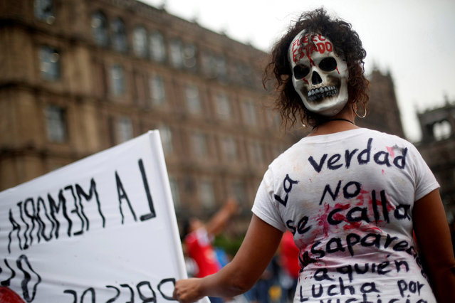 """A demonstrator takes part during a march in commemoration of the 45th anniversary of the Halconazo, when a Mexican paramilitary unit called the Halcones (Falcons) killed an unknown number of students during a demonstration in 1971, in Mexico City, Mexico, June 10, 2016. The mask reads """"It was the state"""". The T-shirt reads """"The truth will not shut up, disappear those who fight"""". (Photo by Edgard Garrido/Reuters)"""