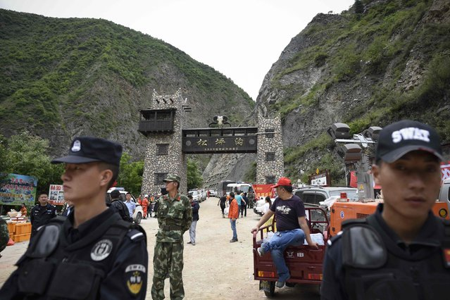 Police stand their guard at an entrance of a road to a landslide area in the village of Xinmo in Maoxian county, China's Sichuan province on June 24, 2017. Rescuers dug through earth and rocks in an increasingly bleak search for more than 90 people still missing a day after their village in southwest China vanished under a huge landslide. (Photo by Wang Zhao/AFP Photo)