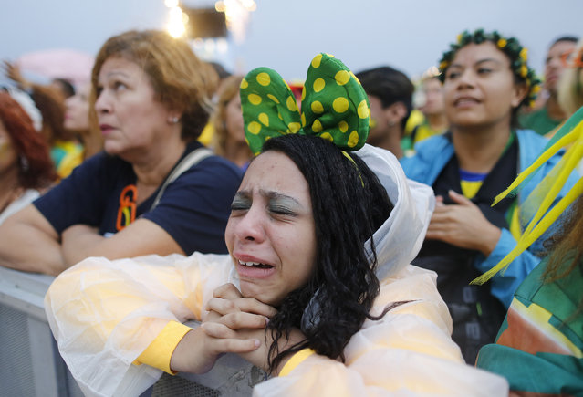 A Brazil soccer fan reacts in frustration as she watches her team play a World Cup semifinal match against Germany on a live telecast inside the FIFA Fan Fest area on Copacabana beach in Rio de Janeiro, Brazil, Tuesday, July 8, 2014. (Photo by Leo Correa/AP Photo)