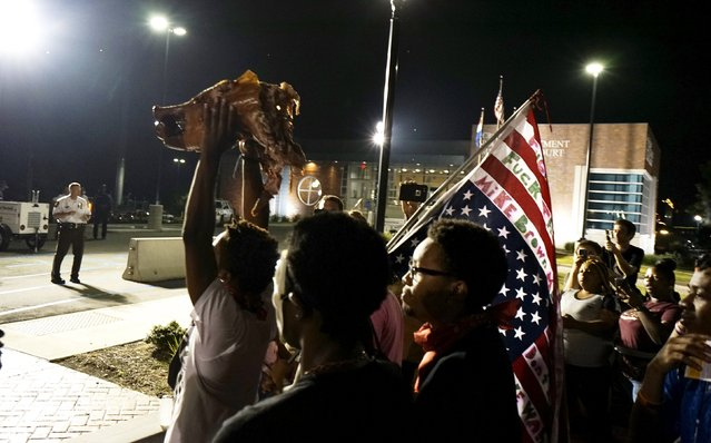 Protesters hold up a pig's head from a pig roast outside the police department in Ferguson, Missouri August 8, 2015. (Photo by Rick Wilking/Reuters)