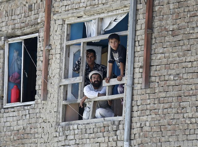 Members of an Afghan family look out from a broken window of a house near the site of a car bomb blast at the entrance gate to the Kabul airport, Afghanistan August 10, 2015. (Photo by Mohammad Ismail/Reuters)