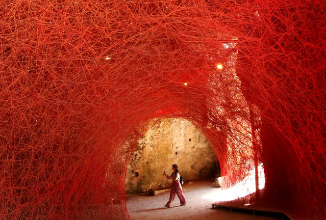"""A visitor views the art installation """"A Walk Through the Line"""" by Japanese artist Chiharu Shiota, that is on display as part of the European Capital of Culture 2017 exhibitions program, in Paphos, Cyprus, 19 July 2017. Since January 2017, the city of Pafos holds the title of the European Capital of Culture 2017, along with Aarhus in Denmark. (Photo by Katia Christodoulou/EPA)"""