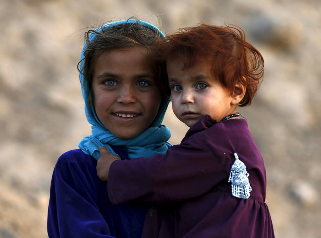 An Afghan girl holds her sister as they stand outside their house in Kabul, Afghanistan August 4, 2015. (Photo by Omar Sobhani/Reuters)