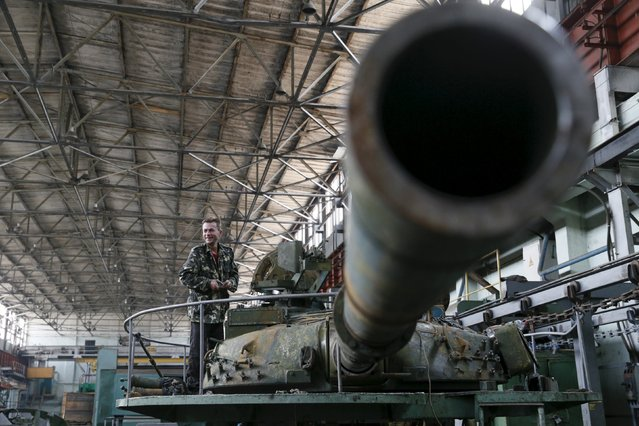 An employee works on a turret as armored vehicles are repaired at the Kiev armored plant, Ukraine, August 14, 2015. (Photo by Valentyn Ogirenko/Reuters)