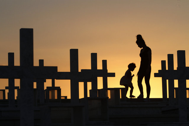 A mother with her child is silhouetted as she visits the graves of Greek and Cypriot soldiers killed in the 1974 Turkish invasion of Cyprus, at the Tymvos Macedonitissas military cemetery in Nicosia, Cyprus, 17 July 2014. Greek and Cypriot soldiers were killed in 1974, 40 years ago, during the Turkish invasion and subsequent occupation of the northern part of the island of Cyprus. (Photo by Katia Christodoulou/EPA)