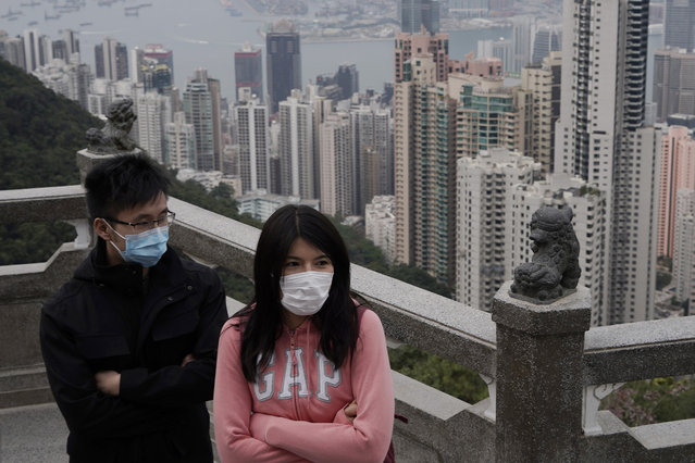 Tourists wear masks at the Peak, a popular tourist spot in Hong Kong, Sunday, February 9, 2020. Health authorities are scrambling to halt the spread of a new virus that has killed hundreds in China, restricting visitors from the country and confining thousands on cruise ships for extensive screening after passengers have tested positive. (Photo by Kin Cheung/AP Photo)