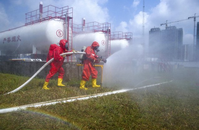 Firefighters in protection suits attend an anti-chemical drill next to storage tanks of liquefied petroleum gas, at a factory in Haikou, Hainan province, China, August 21, 2015. Nationwide inspections of facilities handling dangerous chemicals and explosives were ordered by China's State Council after the blasts at Tianjin port that killed at least 116 people last week. (Photo by Reuters/Stringer)