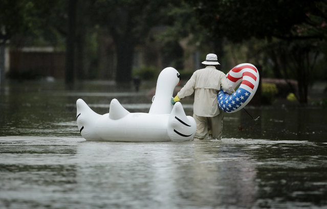 A man walks to his home in a neighborhood inundated by floodwaters from Tropical Storm Harvey on Monday, August 28, 2017, in Houston, Texas. (Photo by Charlie Riedel/AP Photo)