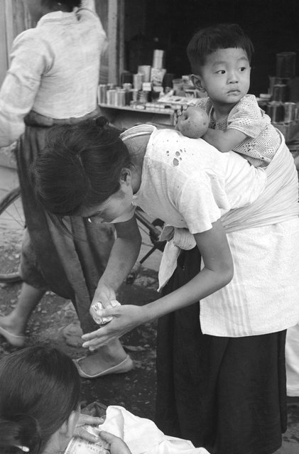 A Korean refugee mother carries her child on her back through the streets of Pusan, the United Nations communications centre during the Korean war, 1950.  (Photo by Bert Hardy)