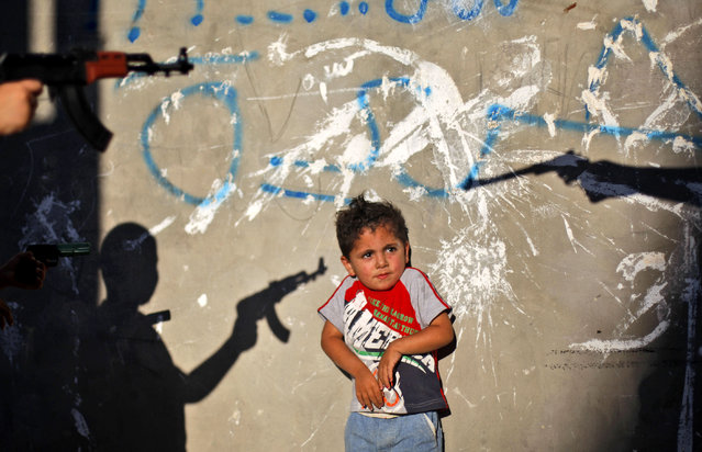 A Palestinian boy reacts as youths frighten him by pointing their toy guns at him, in an alley in the West Bank refugee camp of Al-Amari in Ramallah, Tuesday, June. 16, 2009. (Photo by Muhammed Muheisen/AP Photo)