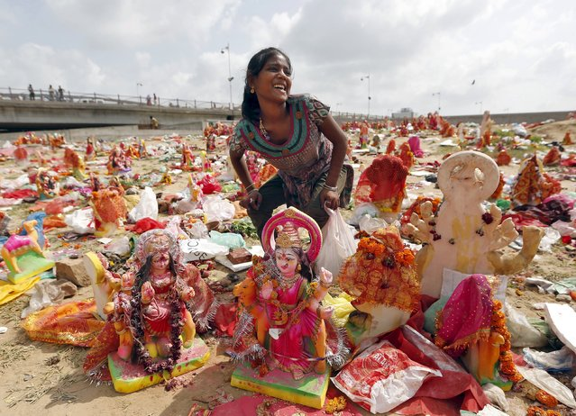 A woman collects idol of Hindu goddess Dashama, left by devotees on the banks of the river Sabarmati on the tenth and final day of the Dashama festival in Ahmedabad, India, August 24, 2015. (Photo by Amit Dave/Reuters)