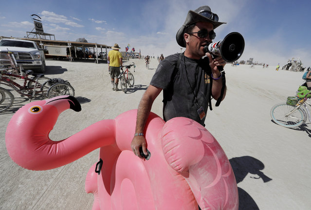 "Burning Man participant Joshua ""Kanizzle"" Cunningham of Burning Man Information Radio gives a running commentary with a megaphone on people's costumes or lack thereof as approximately 70,000 people from all over the world gathered for the annual Burning Man arts and music festival in the Black Rock Desert of Nevada, U.S. August 29, 2017. (Photo by Jim Urquhart/Reuters)"