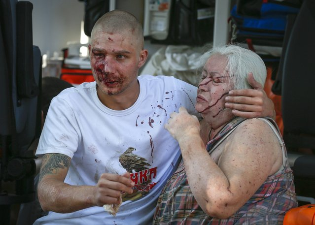 A man and a woman both wounded by what locals say was recent shelling by Ukrainian forces, react as they sit in an ambulance in Donetsk August 23, 2014. (Photo by Maxim Shemetov/Reuters)