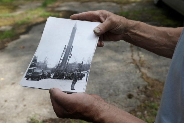 Former Soviet Army officer Vladimir Procenko shows a picture of the Soviet R12 nuclear missile near the abandoned launch site in Zeltini, Latvia, July 22, 2016. (Photo by Ints Kalnins/Reuters)