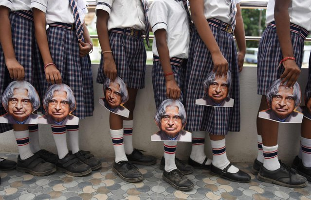 Indian schoolchildren hold masks bearing the image of former Indian president A.P.J Kalam ahead of the first anniversary of his death during a remembrance event at a school in Chennai on July 26, 2016. Former Indian president and Kalam, who played a lead role in the country's nuclear weapons tests, died on July 27, 2015. (Photo by Arun Sankar/Reuters)