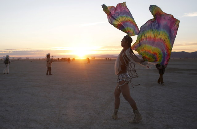 "Rasmus Foyer dances at sunrise during the Burning Man 2015 ""Carnival of Mirrors"" arts and music festival in the Black Rock Desert of Nevada, September 3, 2015. (Photo by Jim Urquhart/Reuters)"