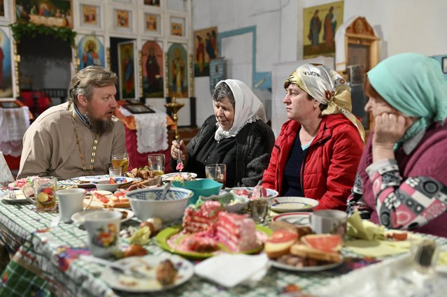 Russian Orthodox priest, Father Nikolai Gensitsky, speaks with believers while having a festive meal during the Easter celebrations in a church in the village of Yekaterininskoye in Omsk Region, Russia on April 19, 2020. (Photo by Alexey Malgavko/Reuters)